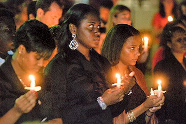 Students observe a moment of silence during the candlelight vigil that drew hundreds.