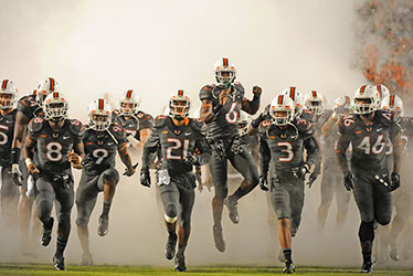 Football Team Running Through Smoke