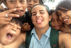 UM graduate Kim Hutchinson hams it up with children in the Philippines