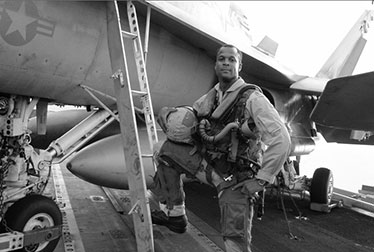William Burns beside his plane on an aircraft carrier deck.
